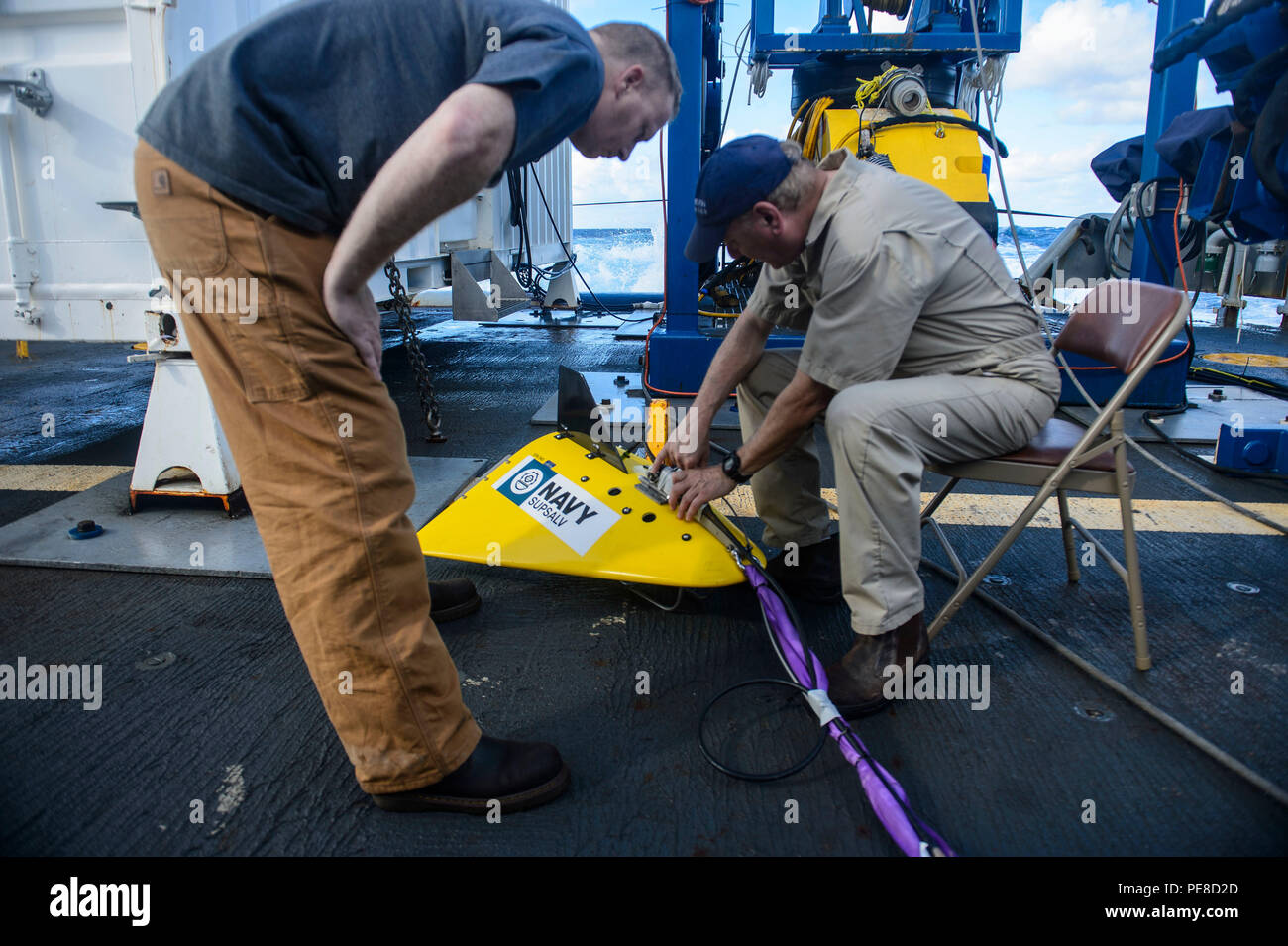 151023-N-RZ218-076   BAHAMAS (Oct. 23, 2015) Ric Sasse (left) and Curt Newport (right), contractors with Phoenix International Incorporated, prepare a tow pinger locater 25 (TPL 25) for the upcoming salvage mission aboard USNS Apache (T-ATF 172). USNS Apache departed Norfolk, Va., Oct. 19, to begin searching for wreckage from the missing U.S. Flagged merchant vessel El Faro. The ship is equipped with several pieces of underwater search equipment, including a voyage data recorder locator, side-scan sonar and an underwater remote operated vehicle. The Navy's mission will be to first locate the s - Stock Image