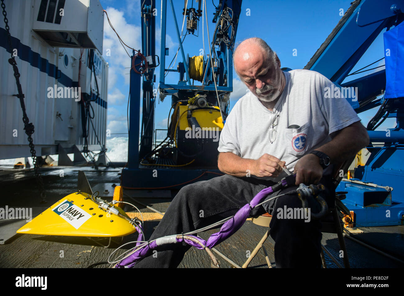 151023-N-RZ218-102  BAHAMAS (Oct. 23, 2015) Mike Unzicker, a contractor with Phoenix International Incorporated, prepare a tow pinger locater 25 (TPL 25) for the upcoming salvage mission aboard USNS Apache (T-ATF 172). USNS Apache departed Norfolk, Va., Oct. 19, to begin searching for wreckage from the missing U.S. Flagged merchant vessel El Faro. The ship is equipped with several pieces of underwater search equipment, including a voyage data recorder locator, side-scan sonar and an underwater remote operated vehicle. The Navy's mission will be to first locate the ship and, if possible, to ret - Stock Image