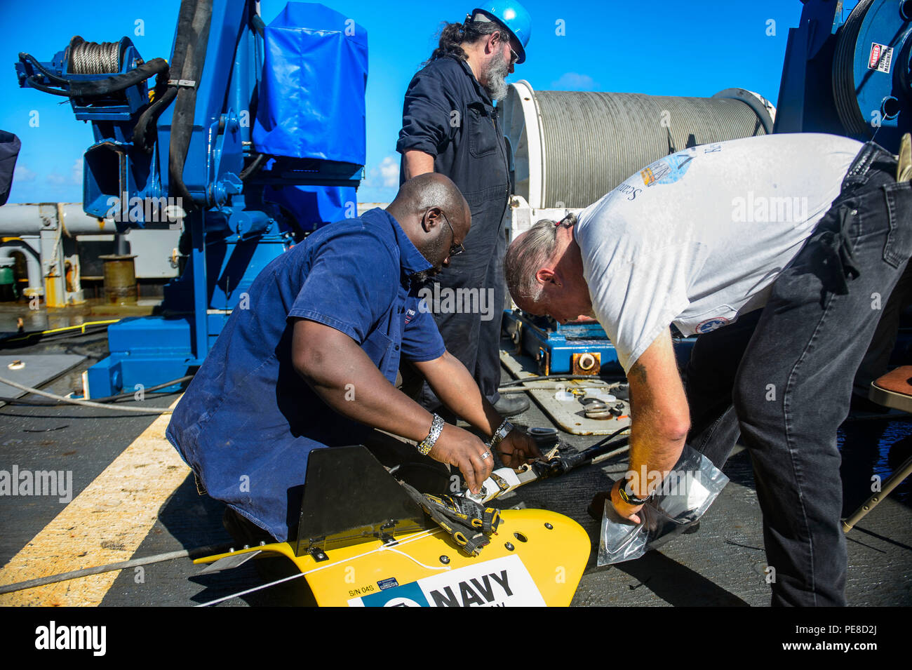 151023-N-RZ218-203   BAHAMAS (Oct. 23, 2015) Contractors with Phoenix International Incorporated prepare a tow pinger locater 25 (TPL 25) for the upcoming salvage mission aboard USNS Apache (T-ATF 172). USNS Apache departed Norfolk, Va., Oct. 19, to begin searching for wreckage from the missing U.S. Flagged merchant vessel El Faro. The ship is equipped with several pieces of underwater search equipment, including a voyage data recorder locator, side-scan sonar and an underwater remote operated vehicle. The Navy's mission will be to first locate the ship and, if possible, to retrieve the voyage - Stock Image