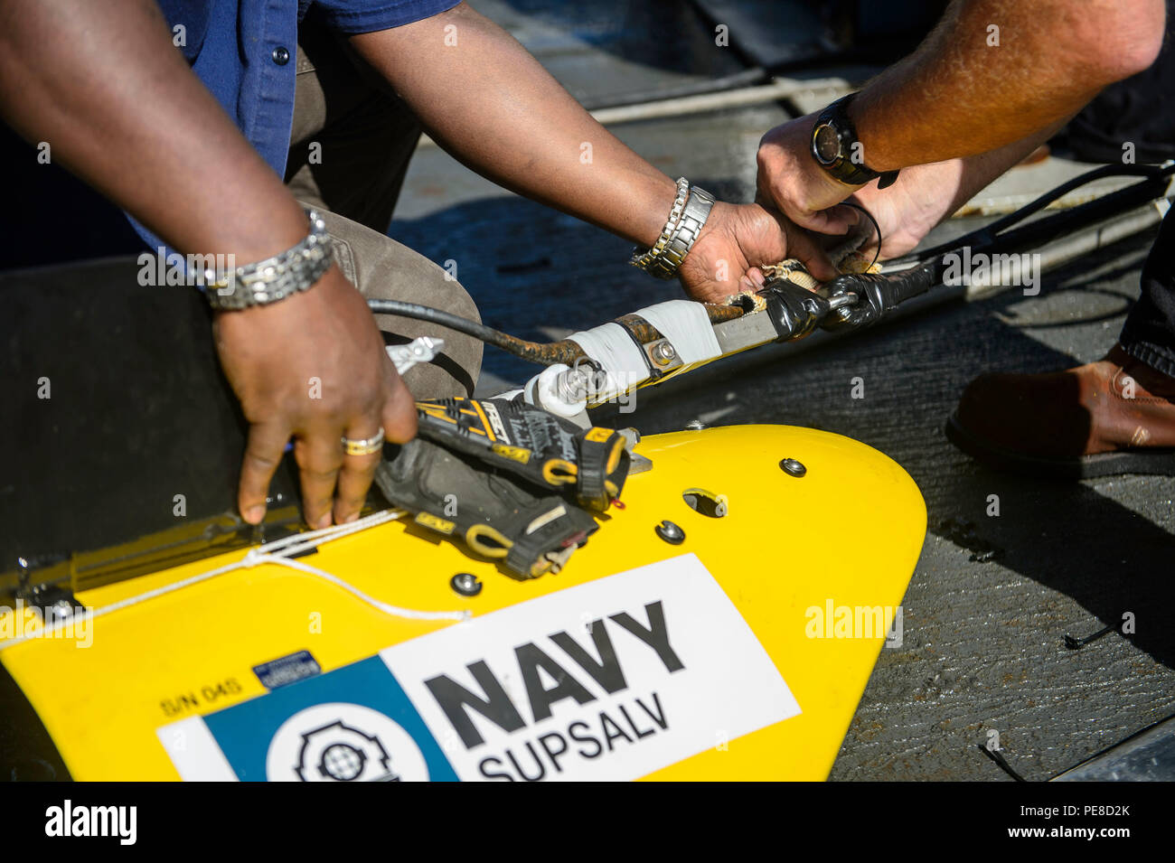 151023-N-RZ218-205   BAHAMAS (Oct. 23, 2015) Contractors with Phoenix International Incorporated prepare a tow pinger locater 25 (TPL 25) for the upcoming salvage mission aboard USNS Apache (T-ATF 172). USNS Apache departed Norfolk, Va., Oct. 19, to begin searching for wreckage from the missing U.S. Flagged merchant vessel El Faro. The ship is equipped with several pieces of underwater search equipment, including a voyage data recorder locator, side-scan sonar and an underwater remote operated vehicle. The Navy's mission will be to first locate the ship and, if possible, to retrieve the voyage - Stock Image