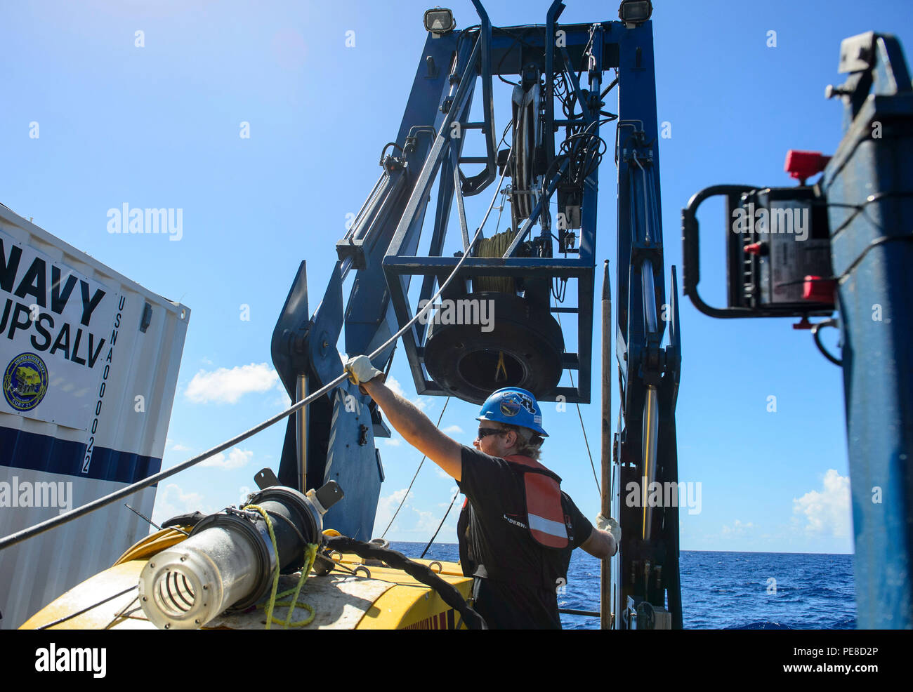 151024-N-RZ218-030   BAHAMAS (Oct. 24, 2015) Tucker Bailey, a contractor with Phoenix International Incorporated, guides a towline through the A-frame while deploying the tow pinger locater 25 (TPL 25) aboard USNS Apache (T-ATF 172). USNS Apache departed Norfolk, Va., Oct. 19, to begin searching for wreckage from the missing U.S. Flagged merchant vessel El Faro. The ship is equipped with several pieces of underwater search equipment, including a voyage data recorder locator, side-scan sonar and an underwater remote operated vehicle. The Navy's mission will be to first locate the ship and, if p - Stock Image