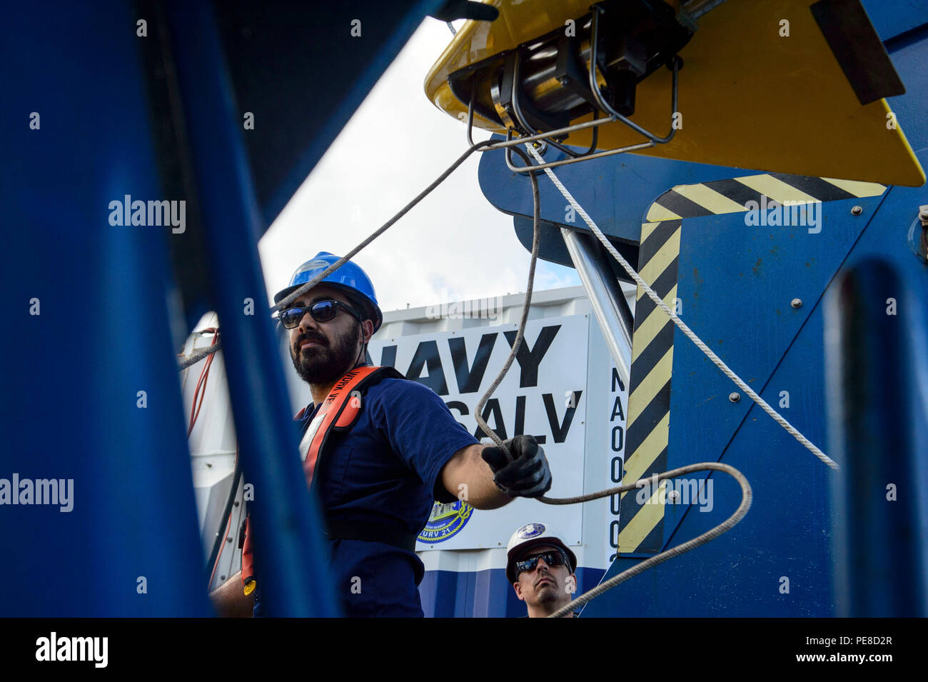 151024-N-RZ218-031   BAHAMAS (Oct. 24, 2015) Steven Benjamin, a contractor with Phoenix International Incorporated, rigs a guideline through the tow pinger locater 25 (TPL 25) aboard USNS Apache (T-ATF 172). USNS Apache departed Norfolk, Va., Oct. 19, to begin searching for wreckage from the missing U.S. Flagged merchant vessel El Faro. The ship is equipped with several pieces of underwater search equipment, including a voyage data recorder locator, side-scan sonar and an underwater remote operated vehicle. The Navy's mission will be to first locate the ship and, if possible, to retrieve the v - Stock Image