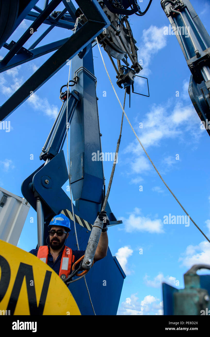 151024-N-RZ218-051   BAHAMAS (Oct. 24, 2015) Steven Benjamin, a contractor with Phoenix International Incorporated, guides the tow pinger locater 25 (TPL 25) up in order to drop it in the water aboard USNS Apache (T-ATF 172). USNS Apache departed Norfolk, Va., Oct. 19, to begin searching for wreckage from the missing U.S. Flagged merchant vessel El Faro. The ship is equipped with several pieces of underwater search equipment, including a voyage data recorder locator, side-scan sonar and an underwater remote operated vehicle. The Navy's mission will be to first locate the ship and, if possible, - Stock Image