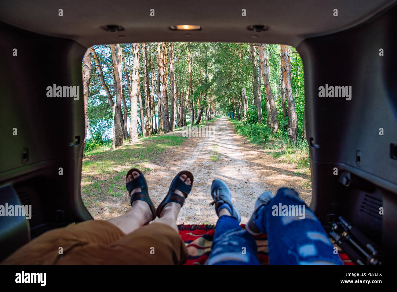 couple laying in suv trunk looking on forest. first person point of view - Stock Image