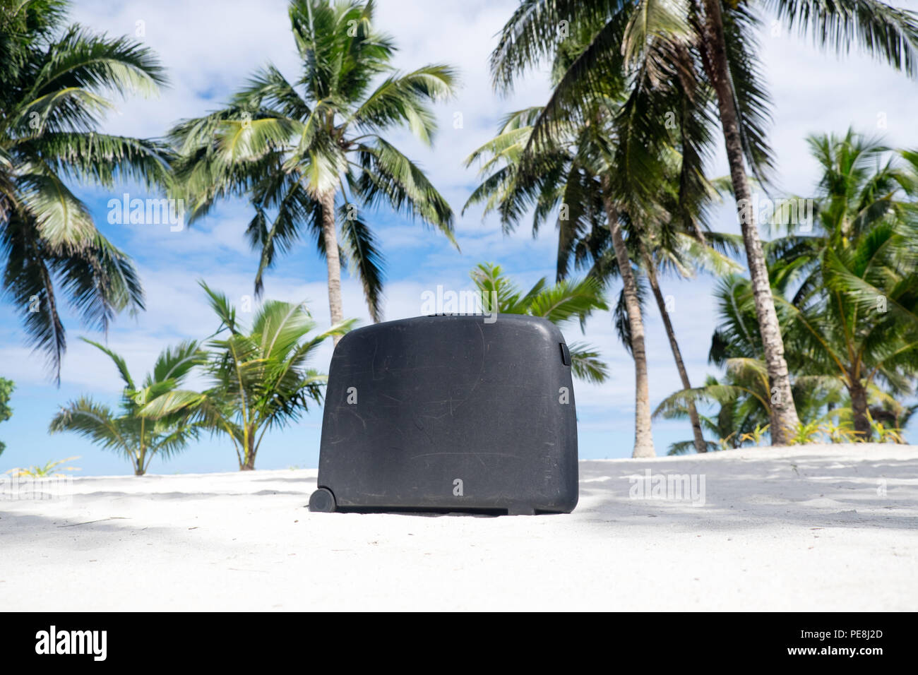 Old, well traveled scratched suitcase on tropical sandy beach with palm trees - Upolu Island, Western Samoa, South Pacific - landscape orientation - Stock Image