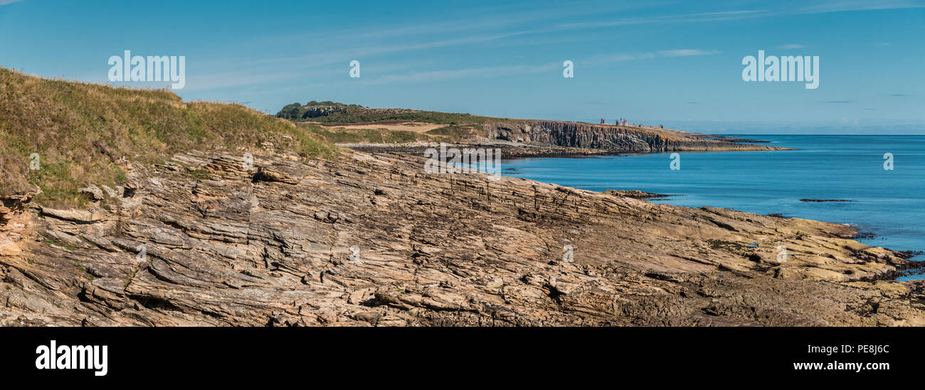 Northumberland Coast AONB panoramic landscape, Cullernose Point and Dunstanburgh Castle from Howick in summer under a clear blue sky - Stock Image