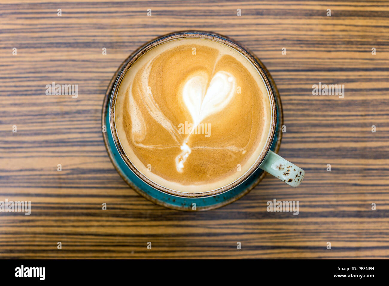 Close-up of coffee latte and cappuccino with heart shape in milk froth in cup as flat lay from above - Stock Image