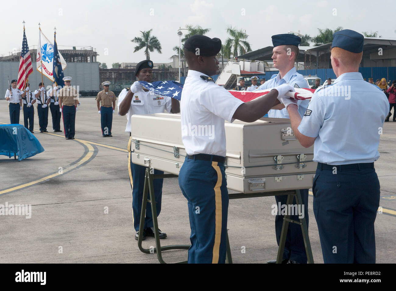 A joint service team prepares to drape an American flag over a casket during a repatriation ceremony at Subang Air Base, Malaysia, Nov. 5, 2015. The 15-member team comprised of members of the Defense POW/MIA Accounting Agency as well service members from U.S. Army Pacific and Pacific Air Force Command, was sent from Hawaii to honor the remains of a fallen service member who paid the ultimate sacrifice when his plane went down over Malaysia in 1945. The ceremony signifies the transfer of the remains from Malaysia back to the U.S. where the service member can be ultimately identified and returne - Stock Image