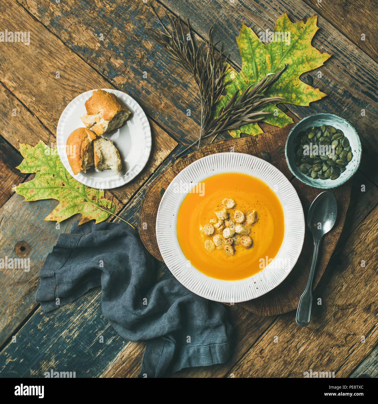 Warming pumpkin cream soup with croutons and seeds, square crop - Stock Image