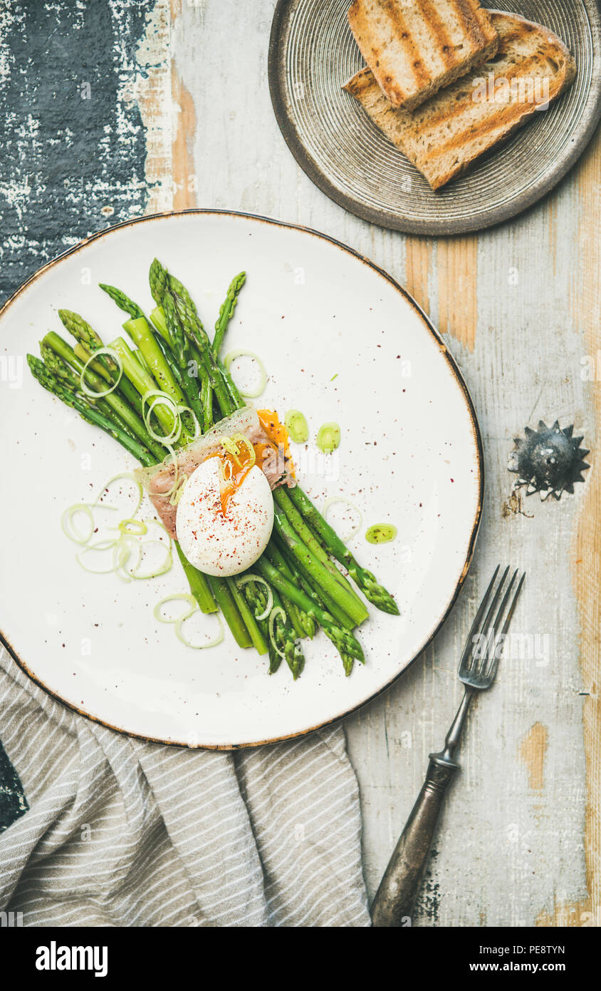 Flat-lay of green asparagus, soft-boiled egg , bacon and toasts - Stock Image