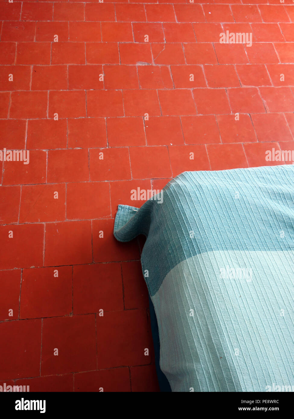 Red floor tiles in a bedroom of a large French village house showing corner of a bed from above - Stock Image