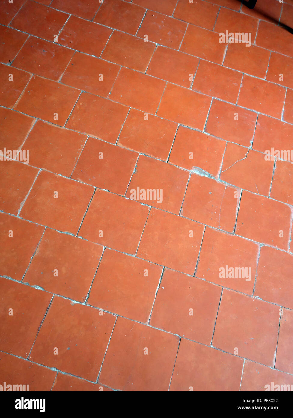 Red antique floor tiles in a large French house - Stock Image