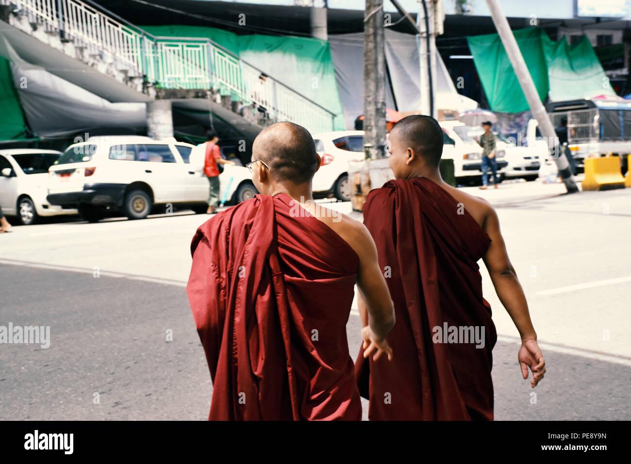 Rwo Buddhist monks crossing the road in Yangon, Myanmar - Stock Image
