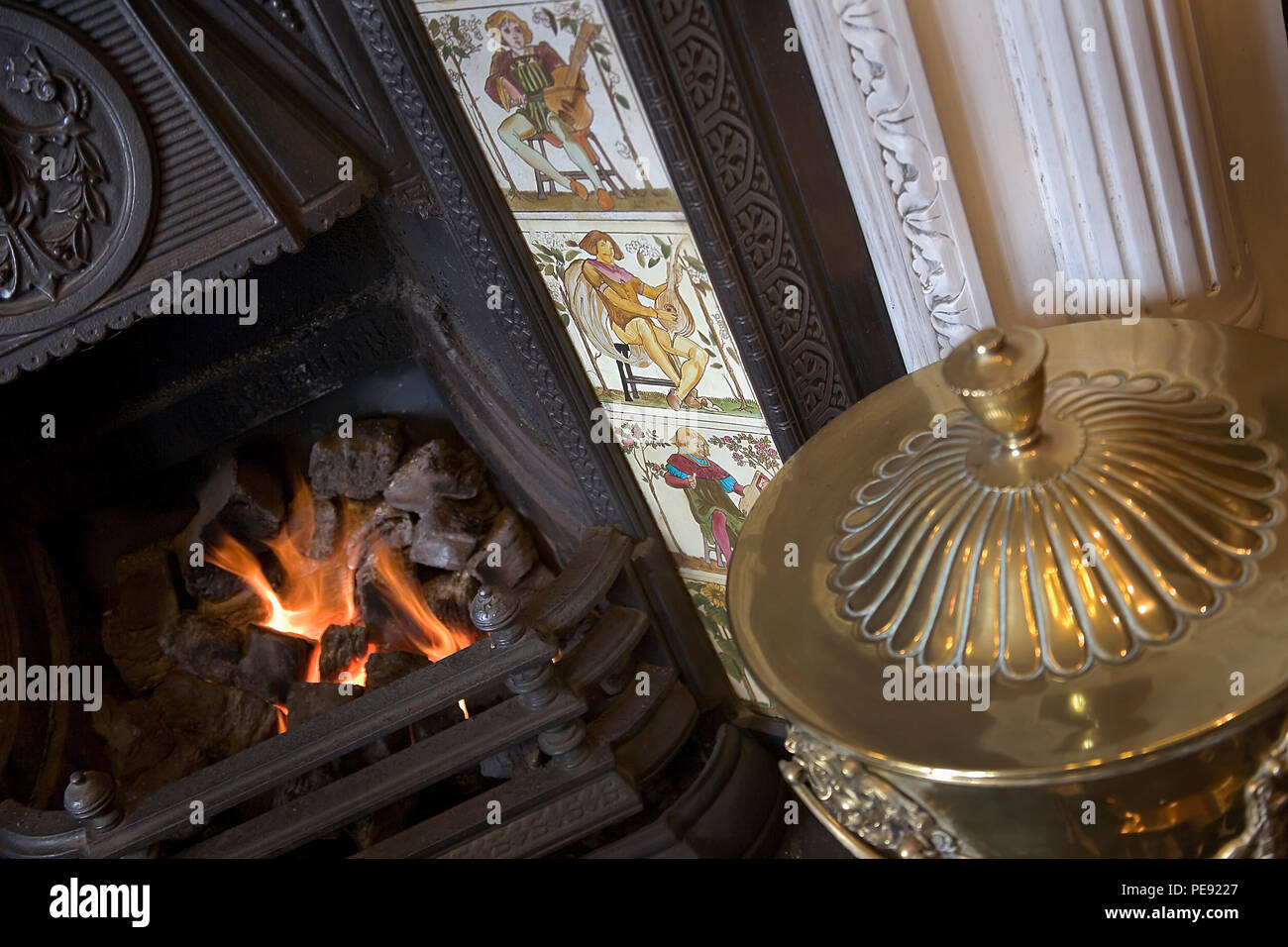 Victorian fireplace with decorative tiles and open fire - Stock Image