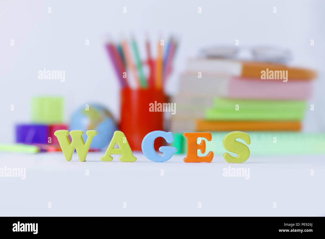 word wages on a blurred background of school supplies .photo with copy space - Stock Image