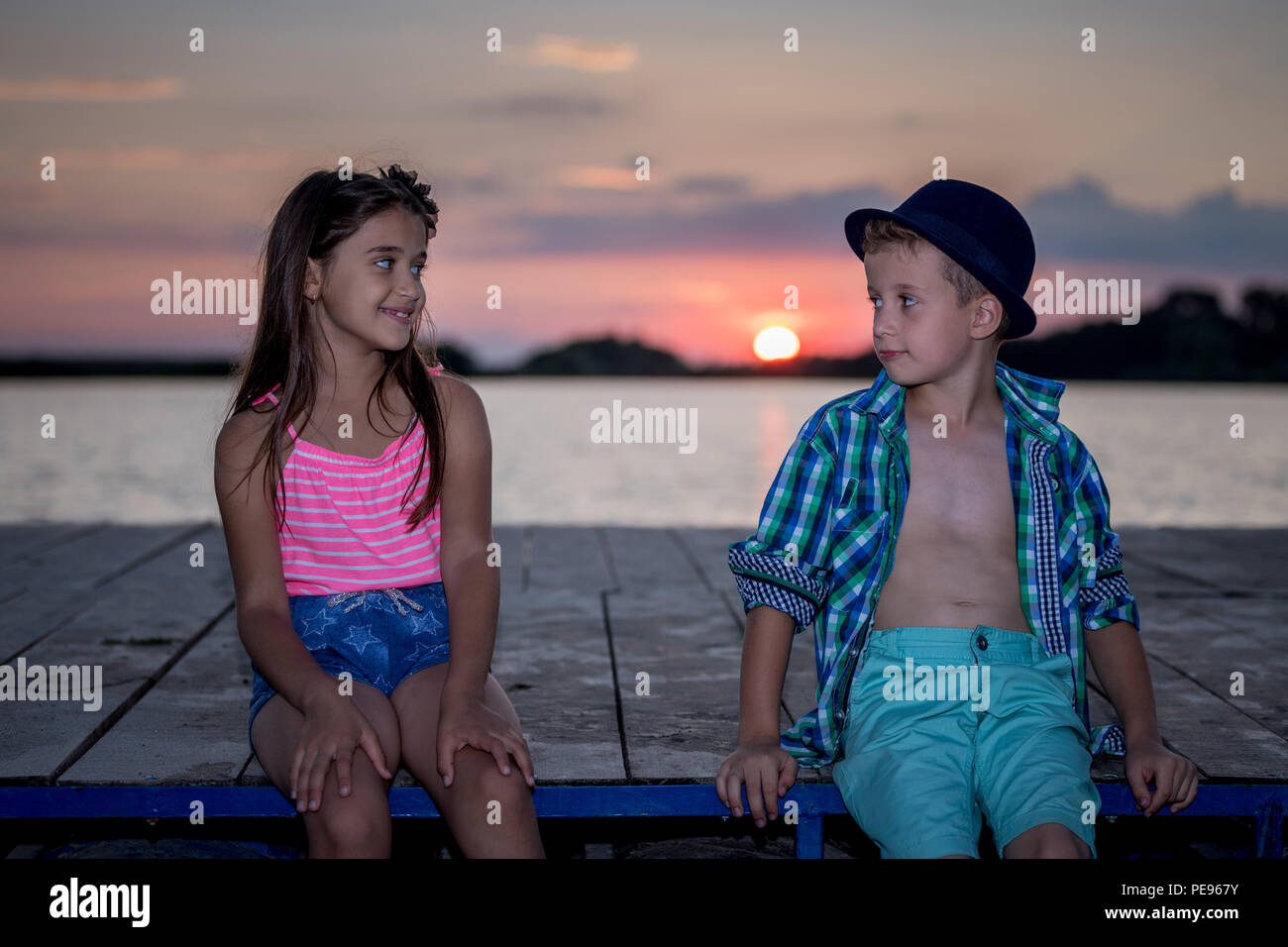 Girl and boy playing on the beach at sunset time. First love.Happy kids enjoying the lake while having a good time. - Stock Image