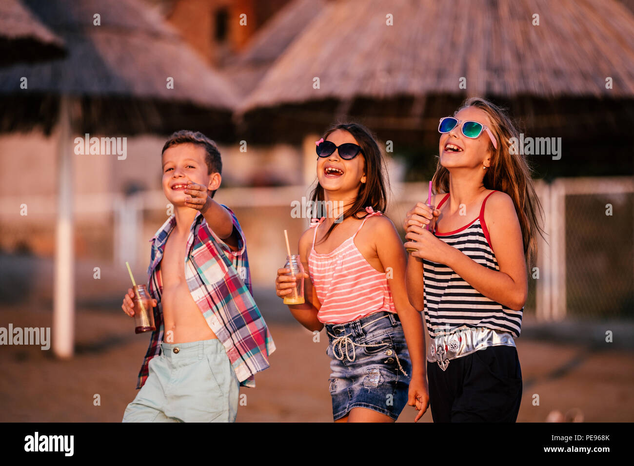 Happy children having fun while walking along a sandy beach. Summer and travel concept - Stock Image