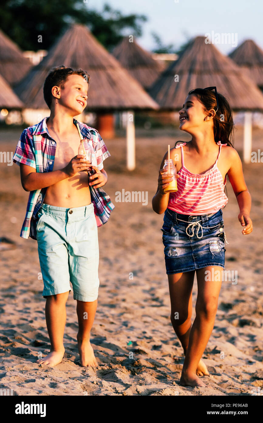 Portrait of happy children while having fun walking on the shore. Summer vacation and healthy lifestyle concept - Stock Image
