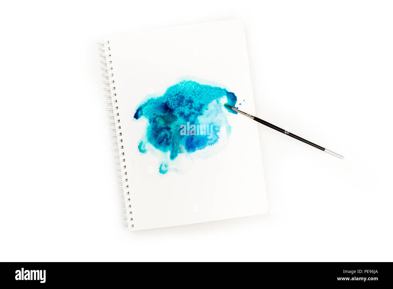 An overhead photo of a watercolor stain in a sketchbook with a brush
