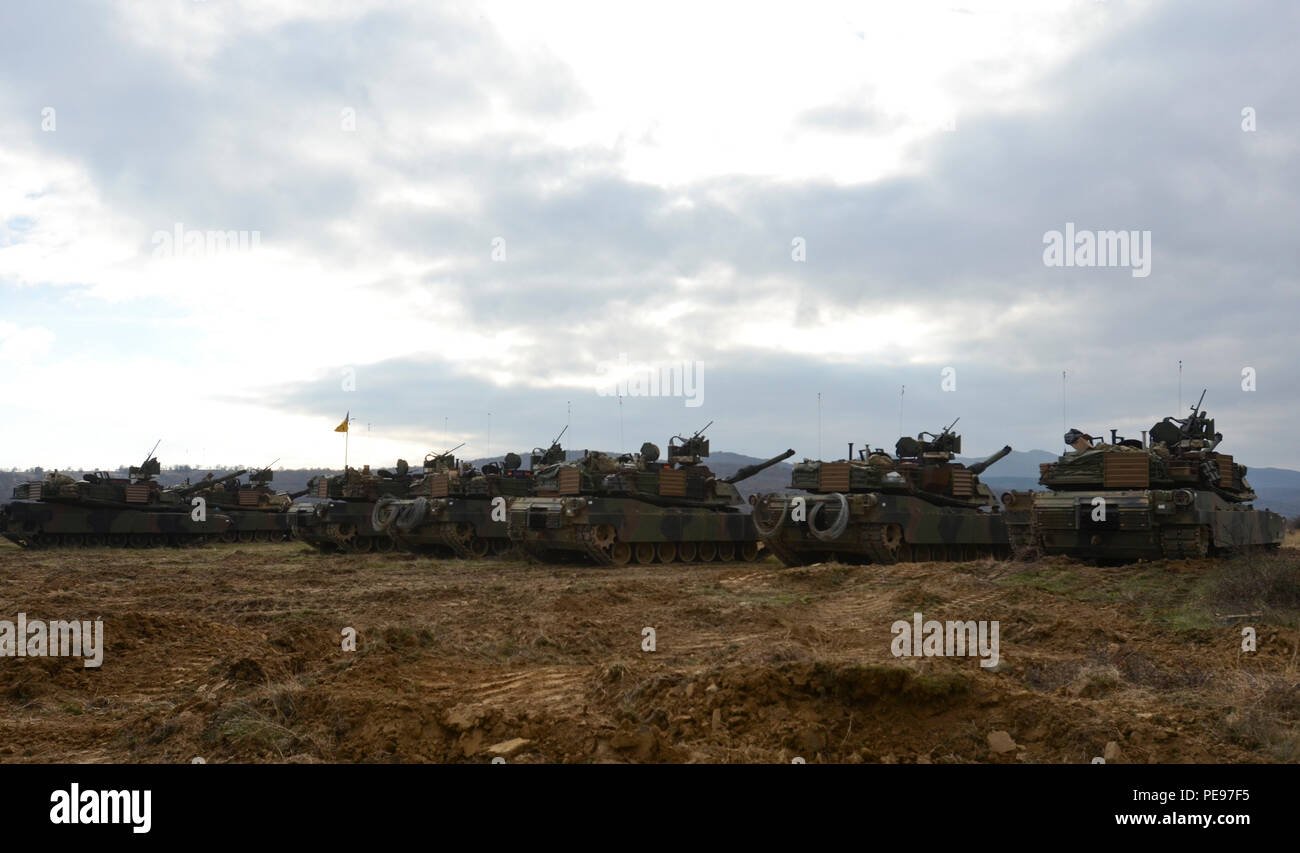 A row of M1A2 System Enhancement Package Version 2 Abrams tanks belonging to 1st Armored Brigade Combat Team, attached to 5th Squadron, 7th Cavalry Regiment, 3rd Infantry Division, stationed at Fort Stewart, Ga., line the horizon during a field training exercise in support of Operation Atlantic Resolve at Novo Selo Training Center, Bulgaria, Nov. 17, 2015. (U.S. Army photo by Staff Sgt. Steven M. Colvin/Released) - Stock Image
