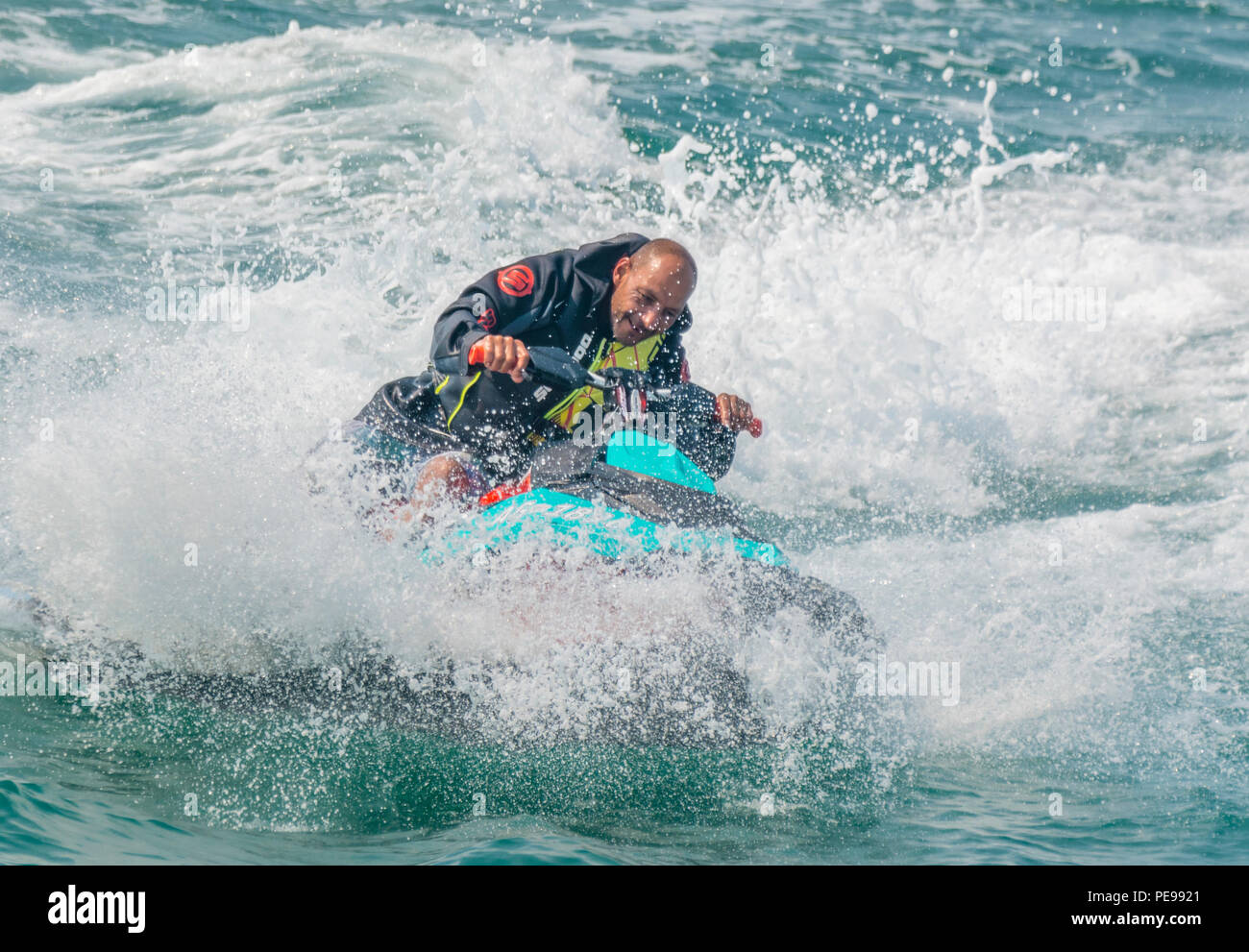 Man riding a jet ski on the sea in Summer in the UK. Water sport.Jet ski. Jet skiing. - Stock Image