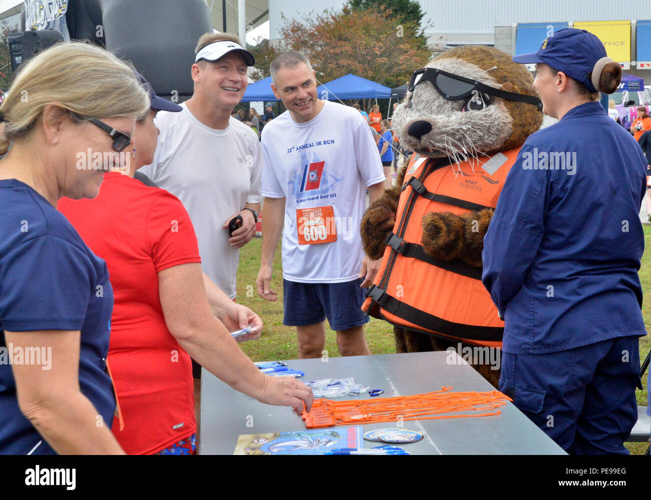 Rear Adm. Steven P. Metruck (left) and Master Chief Petty Officer Mark Pearson (right) talk with shipmates and Sammy the Sea Otter, Saturday, Nov. 7, 2015, during Coast Guard Day festivities in Portsmouth, Va. The city of Portsmouth is a designated Coast Guard City and held a festival to honor the men and women of the service and their families. (Coast Guard photograph by Petty Officer 3rd Class Joshua Canup) Stock Photo