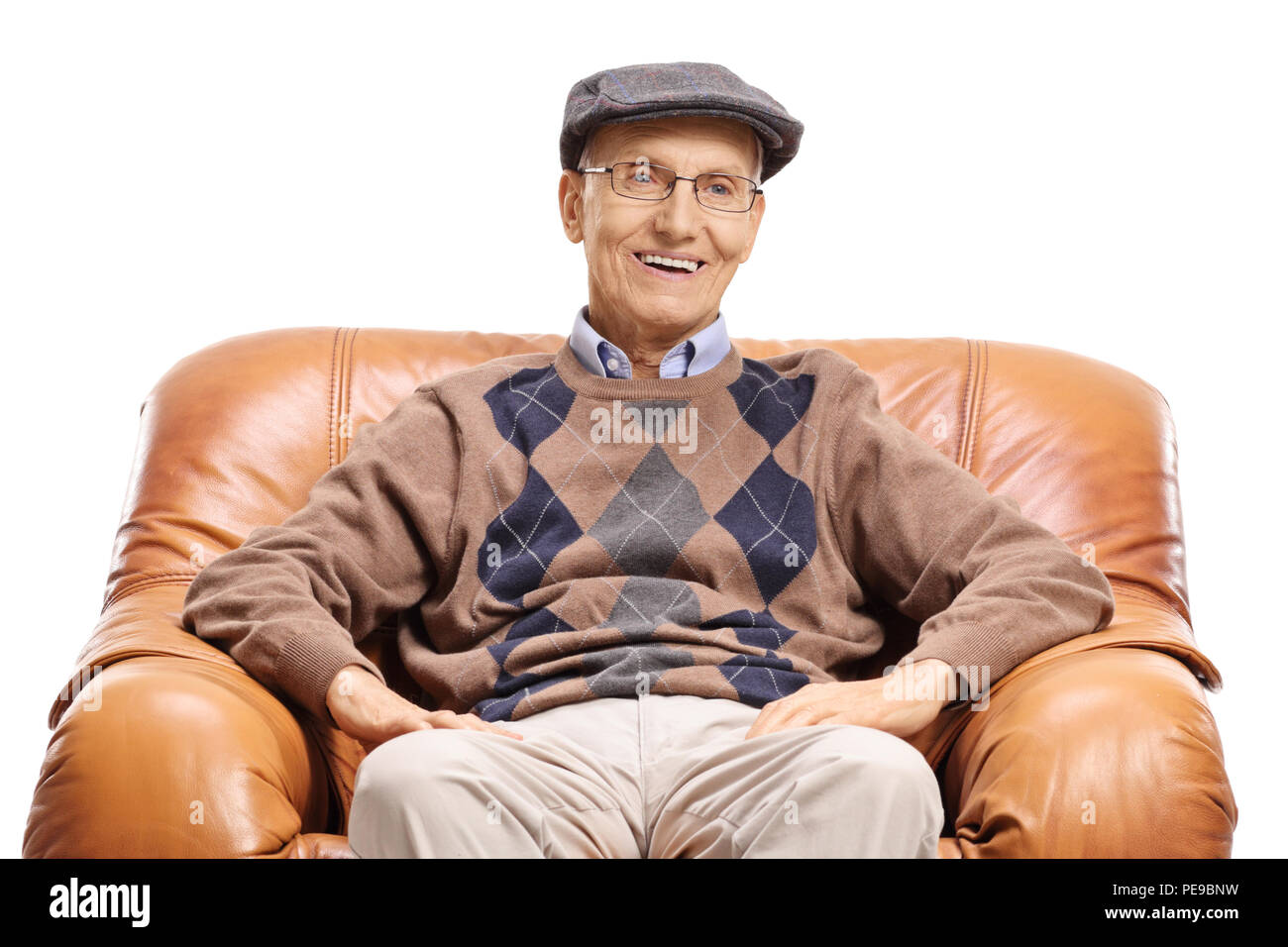 Elderly man sitting in a leather armchair and looking at the camera isolated on white background - Stock Image