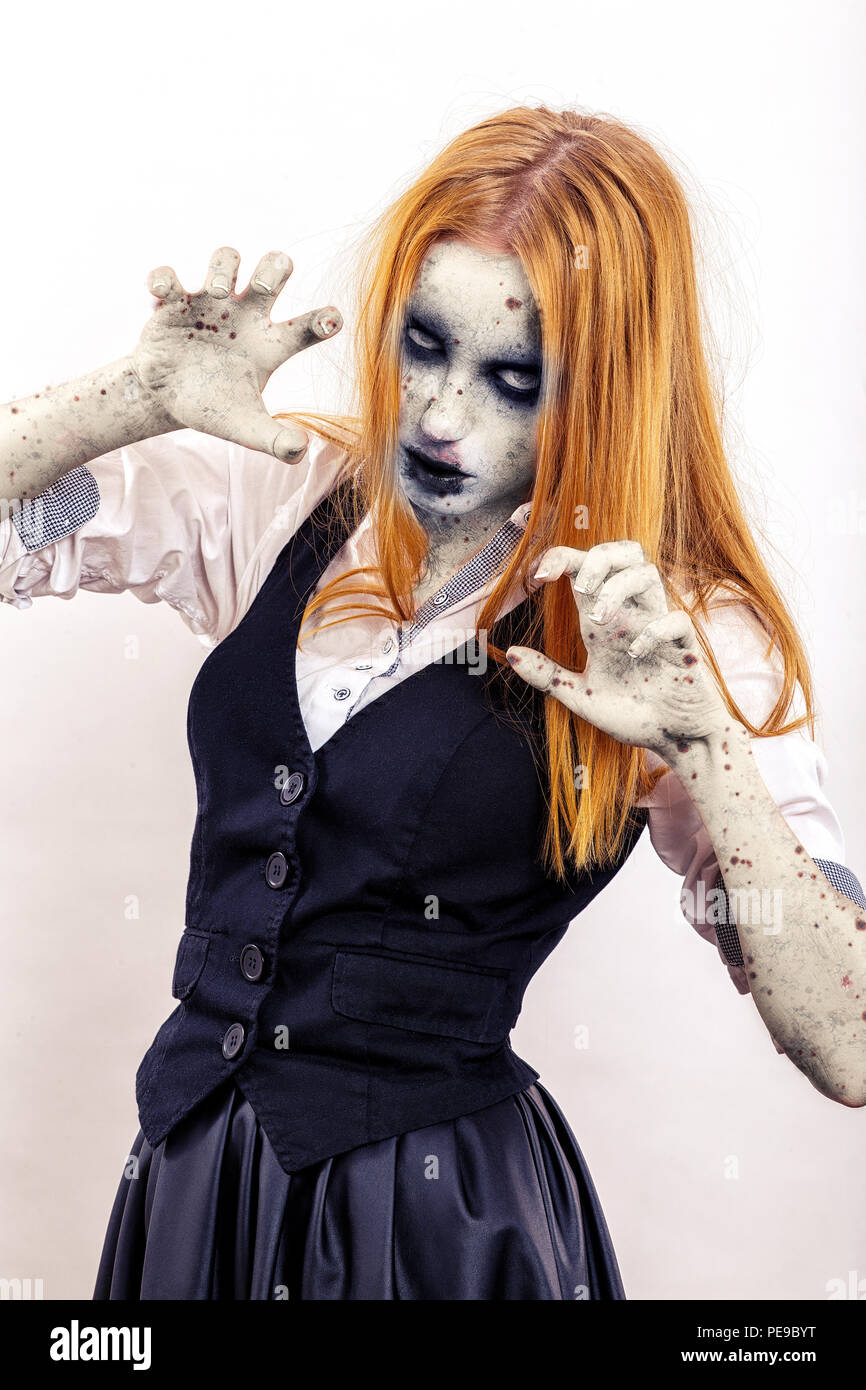 zombie girl attack with yellow hair in attack pose on white background Stock Photo