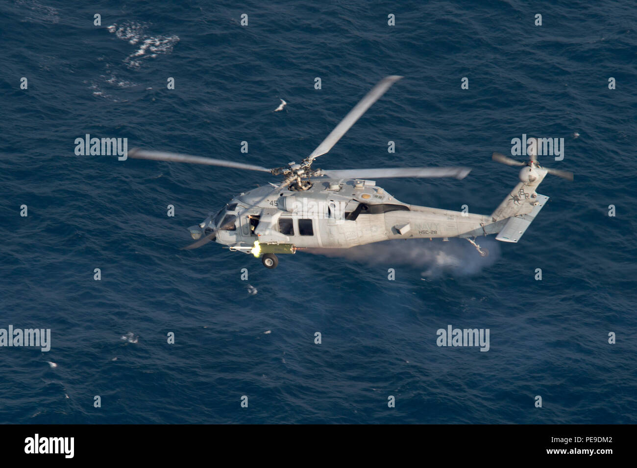 "151114-N-AX638-584 GULF OF ADEN (Nov. 14, 2015) An MH-60S Seahawk, attached to Helicopter Sea Combat Squadron (HSC) 28, the ""Dragon Whales,"" fires an inert 2.75 inch 'Mighty Mouse' rocket during a rocket exercise. HSC-28 is embarked aboard the amphibious assault ship USS Kearsarge (LHD 3) as part the Kearsarge Amphibious Ready Group (ARG), and with the embarked 26th Marine Expeditionary Unit (MEU), is deployed in support of maritime security operations and theater security cooperation efforts in the U.S. 5th Fleet area of operations. (U.S. Navy photo by Mass Communication Specialist Seaman Tyl - Stock Image"
