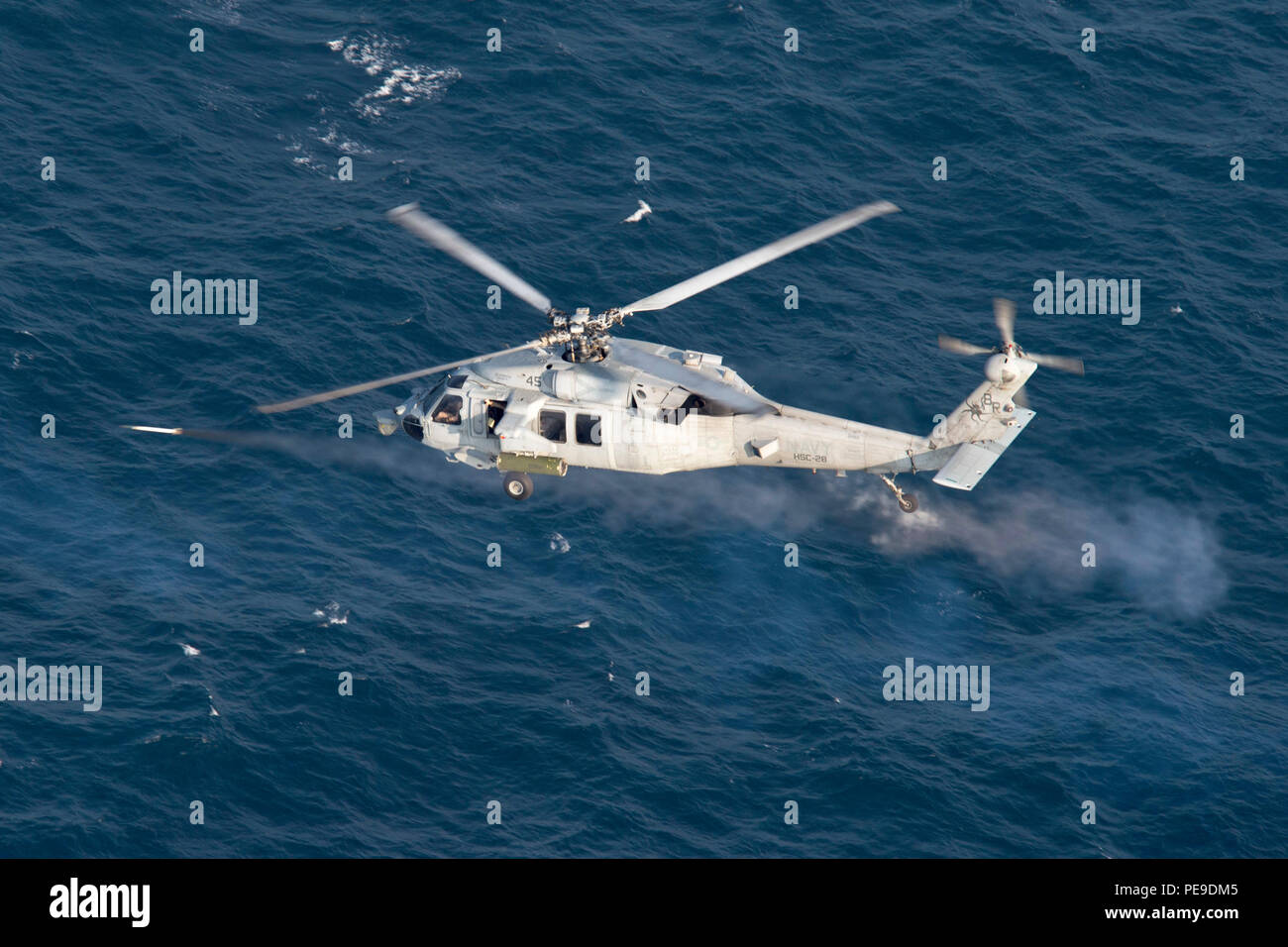 "151114-N-AX638-585 GULF OF ADEN (Nov. 14, 2015) An MH-60S Seahawk, attached to Helicopter Sea Combat Squadron (HSC) 28, the ""Dragon Whales,"" fires an inert 2.75 inch 'Mighty Mouse' rocket during a rocket exercise. HSC-28 is embarked aboard the amphibious assault ship USS Kearsarge (LHD 3) as part the Kearsarge Amphibious Ready Group (ARG), and with the embarked 26th Marine Expeditionary Unit (MEU), is deployed in support of maritime security operations and theater security cooperation efforts in the U.S. 5th Fleet area of operations. (U.S. Navy photo by Mass Communication Specialist Seaman Tyl - Stock Image"