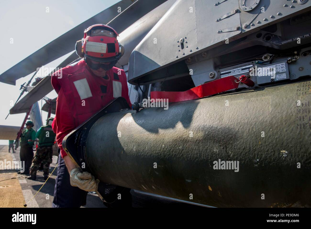 151114-N-KW492-033 GULF OF ADEN (Nov. 14, 2015) Aviation Ordnanceman 3rd Class Matthew Maikell, from Spring Town, Texas, takes a shield off of a pod of inert 2.75 inch 'Mighty Mouse' rockets attached to an MH-60S Seahawk aboard the amphibious assault ship USS Kearsarge (LHD 3). Kearsarge is the flagship for the Kearsarge Amphibious Ready Group (ARG) and, with the embarked 26th Marine Expeditionary Unit (MEU), is deployed in support of maritime security operations and theater security cooperation efforts in the U.S. 5th Fleet area of operations. (U.S. Navy photo by Mass Communication Specialist - Stock Image