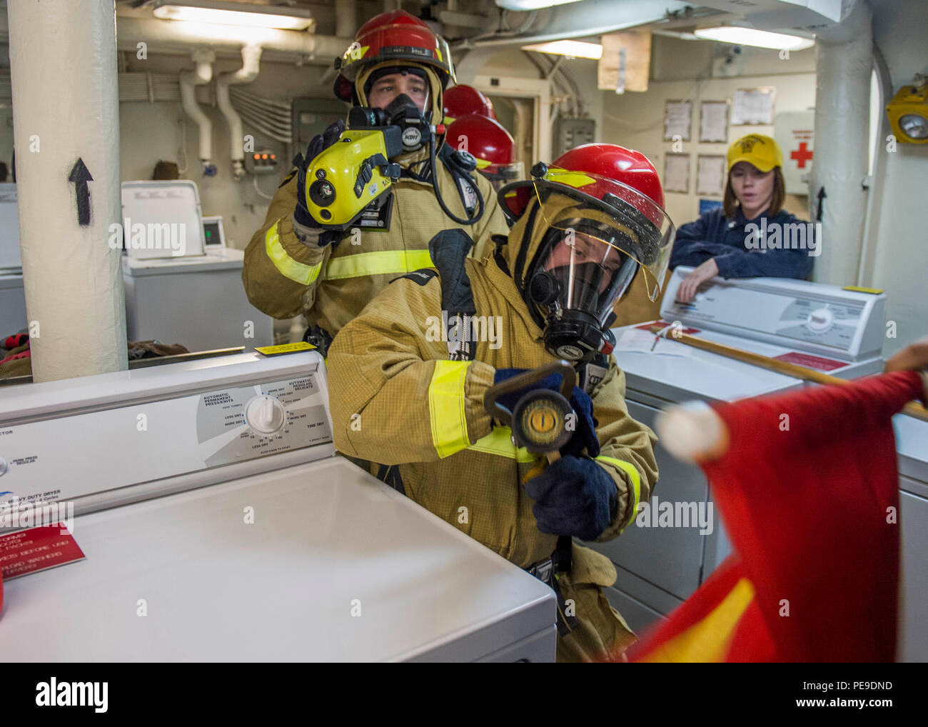 151115-N-YL073-105 GULF OF ADEN (Nov. 15, 2015) Logistics Specialist 3rd Class Nolan Prinze, from Stockton, Calif., front, and Damage Controlman Fireman Heath Simpson, from Castalian Springs, Tenn., fight a simulated fire during a general quarters drill aboard the amphibious assault ship USS Kearsarge (LHD 3). Kearsarge is the flagship for the Kearsarge Amphibious Ready Group (ARG) and, with the embarked 26th Marine Expeditionary Unit (MEU), is deployed in support of maritime security operations and theater security cooperation efforts in the U.S. 5th Fleet area of operations. (U.S. Navy photo - Stock Image