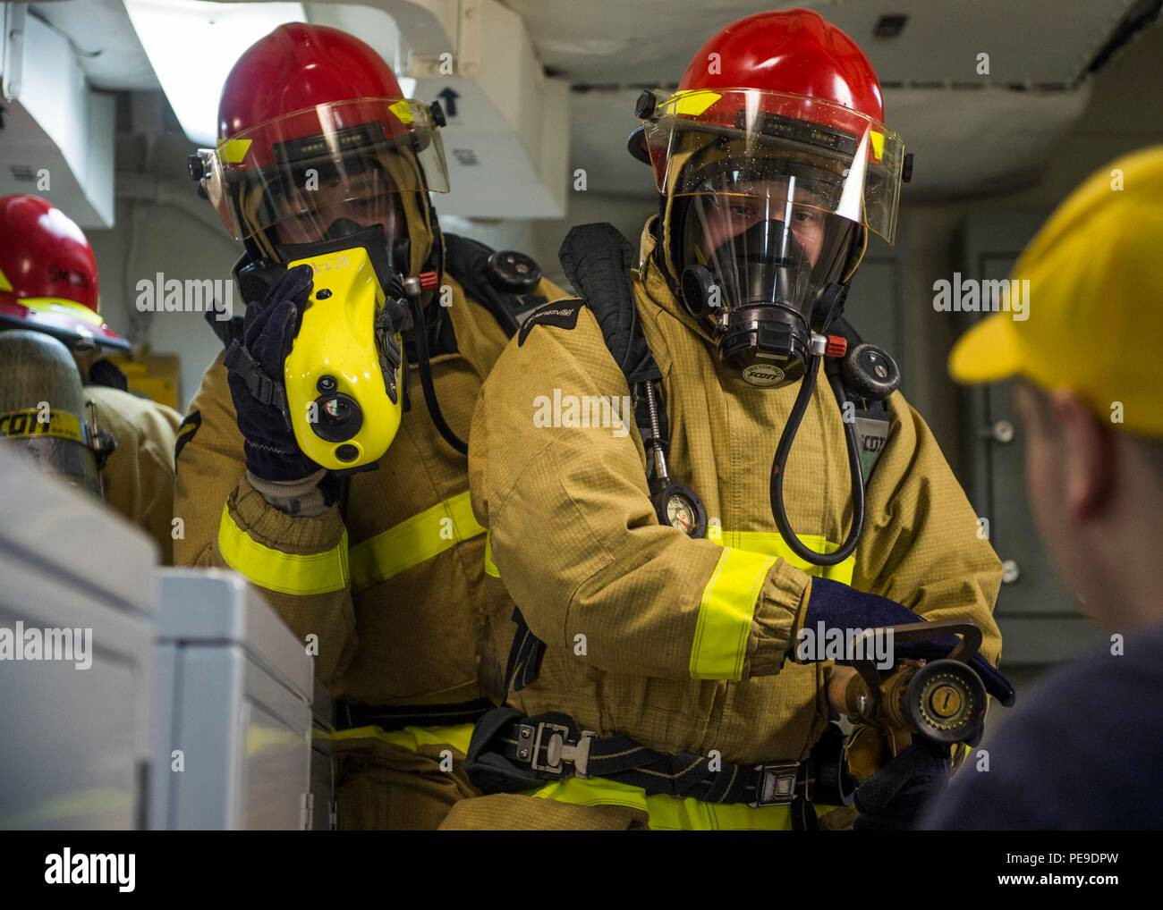 151115-N-YL073-116 GULF OF ADEN (Nov. 15, 2015) Logistics Specialist 3rd Class Nolan Prinze, from Stockton, Calif., and Damage Controlman Fireman Heath Simpson, from Castalian Springs, Tenn., receive firefighting technique training during a general quarters drill aboard the amphibious assault ship USS Kearsarge (LHD 3). Kearsarge is the flagship for the Kearsarge Amphibious Ready Group (ARG) and, with the embarked 26th Marine Expeditionary Unit (MEU), is deployed in support of maritime security operations and theater security cooperation efforts in the U.S. 5th Fleet area of operations. (U.S.  - Stock Image