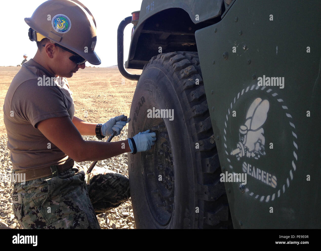 151108-N-SL238-945 SAN CLEMENTE ISLAND, Calif. (Nov. 8, 2015) Equipment Operator Constructionman Monica Cervantes, of Aransas Pass, Texas, assigned to Naval Mobile Construction Battalion (NMCB) 3, checks the tire pressure on a High Mobility Multipurpose Wheeled Vehicle (HMMWV) at the San Clemente Island Seabee Quarry. NMCB 3 is conducting maintenance on all equipment to ensures that operations continue to be conducted safely. (U.S. Navy photo by Engineering Aide 3rd Class Joshua Goldstein/Released) - Stock Image