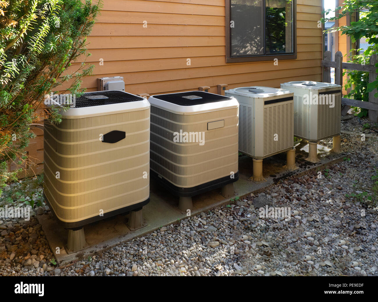 Air conditioning units outside an apartment complex - Stock Image