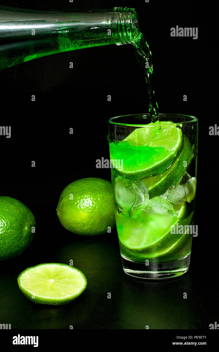 Glass of cold green lemonade with ice and fresh ripe green limes on black background. Homemade lemonade. Mojito or tarragon cocktail. Spring and summe - Stock Image