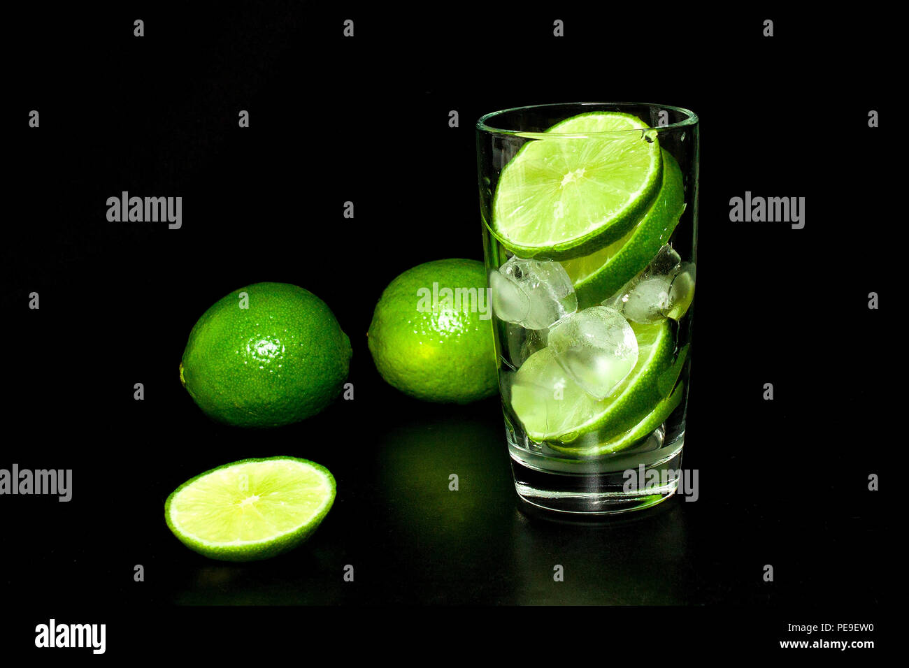 Glass with ice and fresh ripe green limes on black background. Preparation of lemonade. Mojito cocktail. Spring and summer refreshing and beverages co - Stock Image