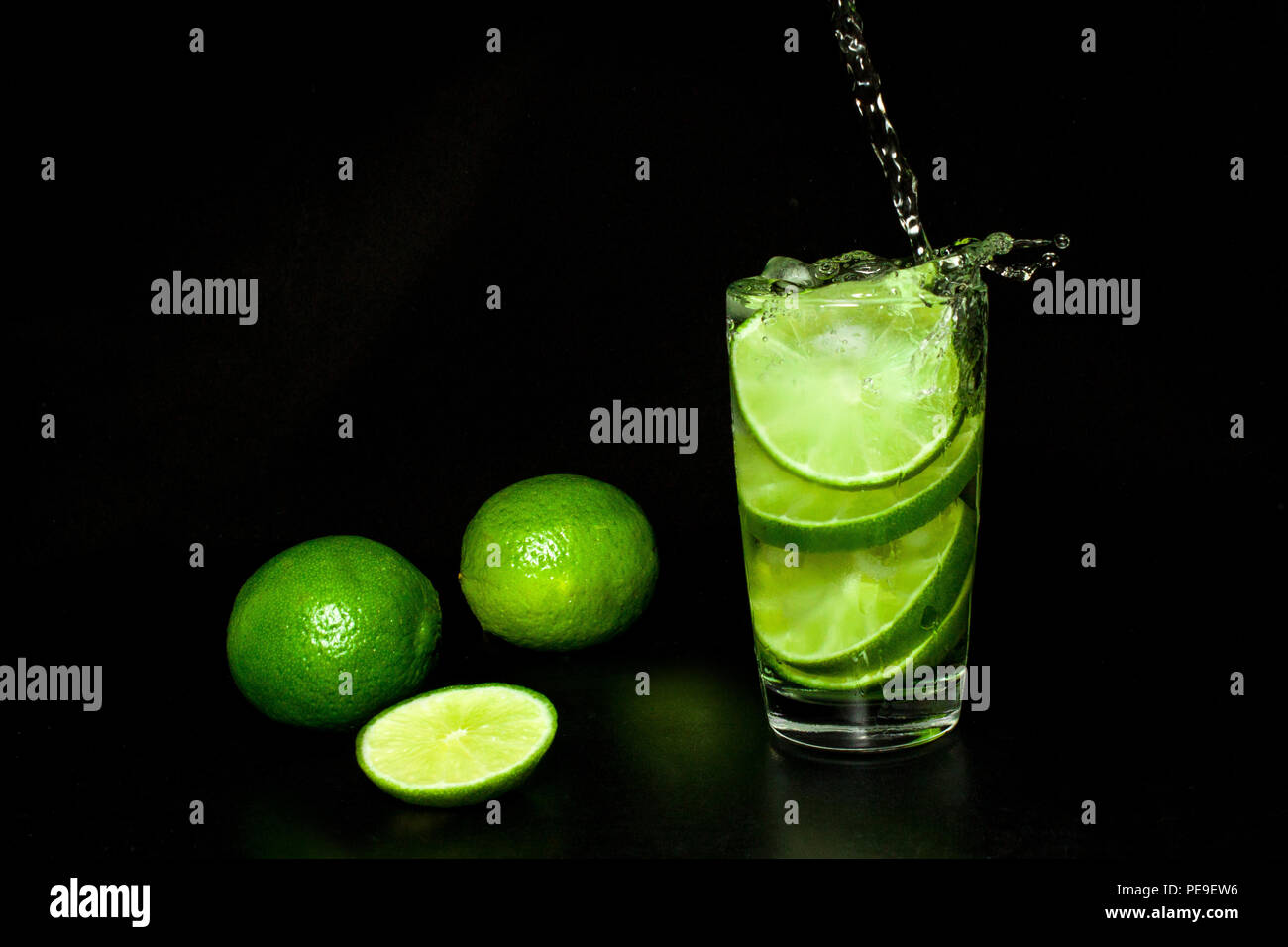 Summer refreshing and beverages concept. Glass of cold drink with ice and fresh ripe slice green limes on black background. Homemade lemonade. Mojito  - Stock Image
