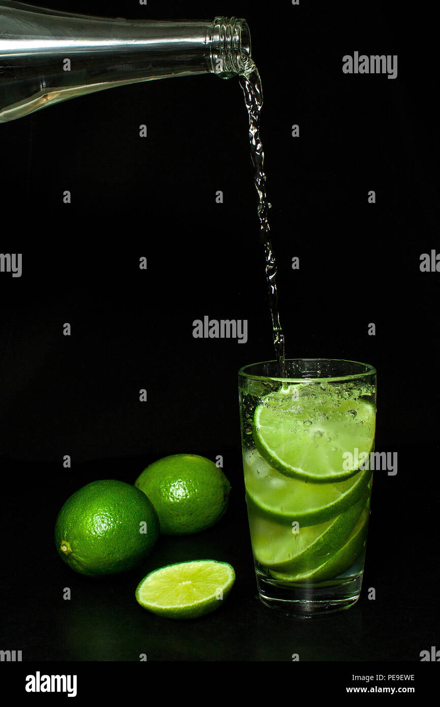 Summer refreshing and beverages concept. Stream of cold water from a bottle is poured into a glass with ice and fresh ripe slice green limes on black  - Stock Image