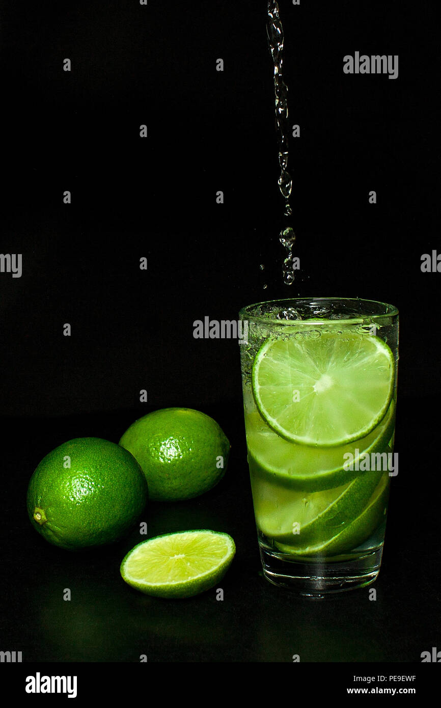 Summer refreshing and beverages concept. Stream of water is poured into Glass of cold drink with ice and fresh ripe slice green limes on black backgro - Stock Image