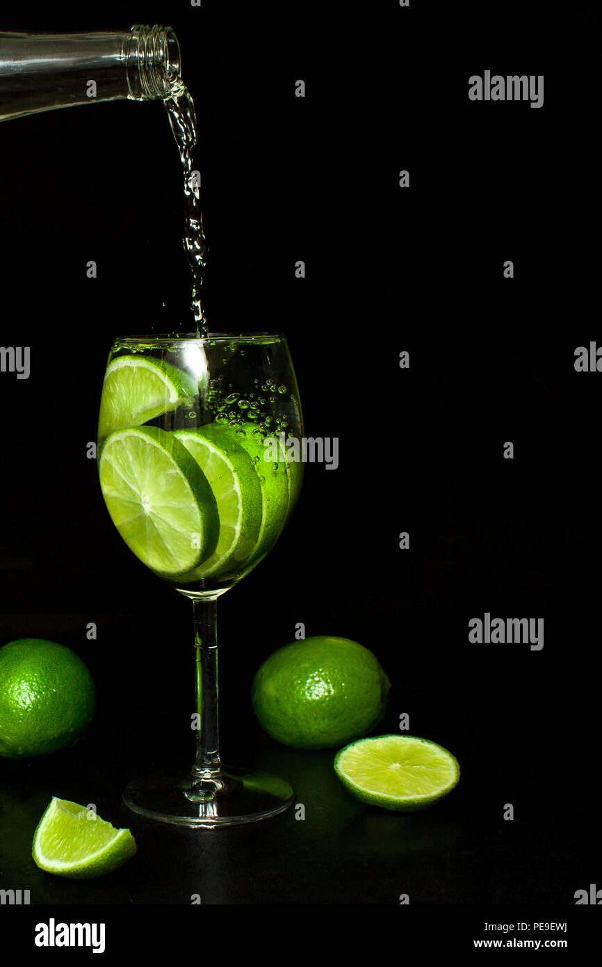 Stream of cold water from a bottle is poured into a wineglass to make cold drink with ice and fresh ripe slice green limes on black background. Mojito - Stock Image