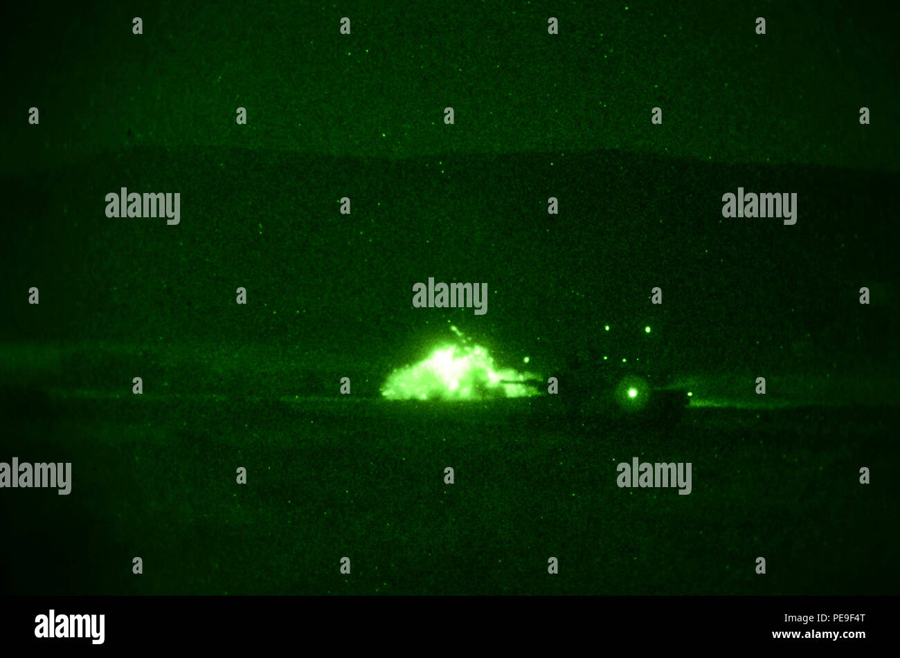Soldiers of 1st Armored Brigade Combat Team, attached to 5th Squadron, 7th Cavalry Regiment, 3rd Infantry Division, stationed at Fort Stewart, Ga., fire a round out of an M1A2 System Enhancement Package Version 2 Abram Tank at enemy targets during a night operations field training exercise in support of Operation Atlantic Resolve at Novo Selo Training Center, Bulgaria, Nov. 17, 2015. (U.S. Army photo by Staff Sgt. Steven M. Colvin/Released) - Stock Image