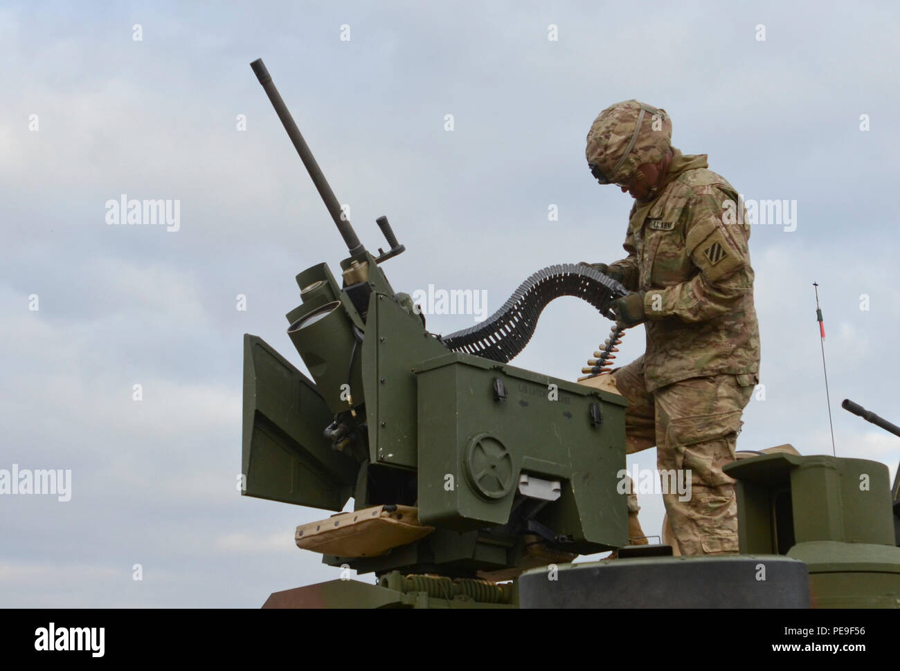 Sgt. Lawrence Cox, an M1A2 System Enhancement Package Version 2 Abrams tank commander of 1st Armored Brigade Combat Team, attached to 5th Squadron, 7th Cavalry Regiment, 3rd Infantry Division, stationed at Fort Stewart, Ga., originally from Lufkin, Texas, loads .50 caliber rounds into the M101 Common Remotely Operated Weapon Station (CROWS) during a field training exercise in support of Operation Atlantic Resolve at Novo Selo Training Center, Bulgaria, Nov. 17, 2015. (U.S. Army photo by Staff Sgt. Steven M. Colvin/Released) - Stock Image