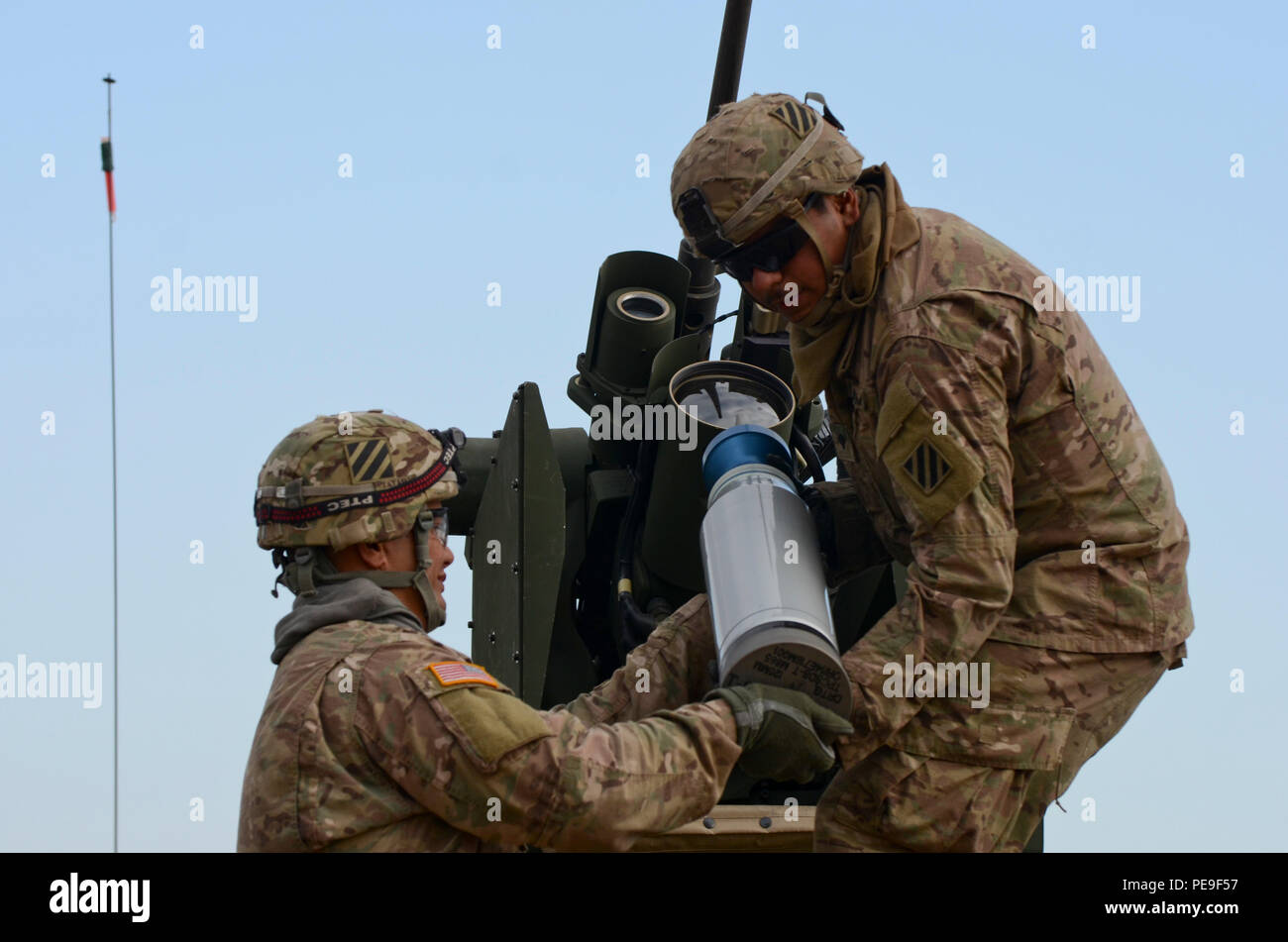2nd Lt. Hemaloto Tatafu, a Delta platoon leader, from Kahuku, Hawaii, hands a 120mm round to Spc. Miguel Romero, an M1A2 System Enhancement Package Version 2 Abram Tank gunner, originally from Los Angeles, both of 1st Armored Brigade Combat Team, attached to 5th Squadron, 7th Cavalry Regiment, 3rd Infantry Division, stationed at Fort Stewart, Ga., during a field training exercise in support of Operation Atlantic Resolve at Novo Selo Training Center, Bulgaria, Nov. 17, 2015. (U.S. Army photo by Staff Sgt. Steven M. Colvin/Released) - Stock Image