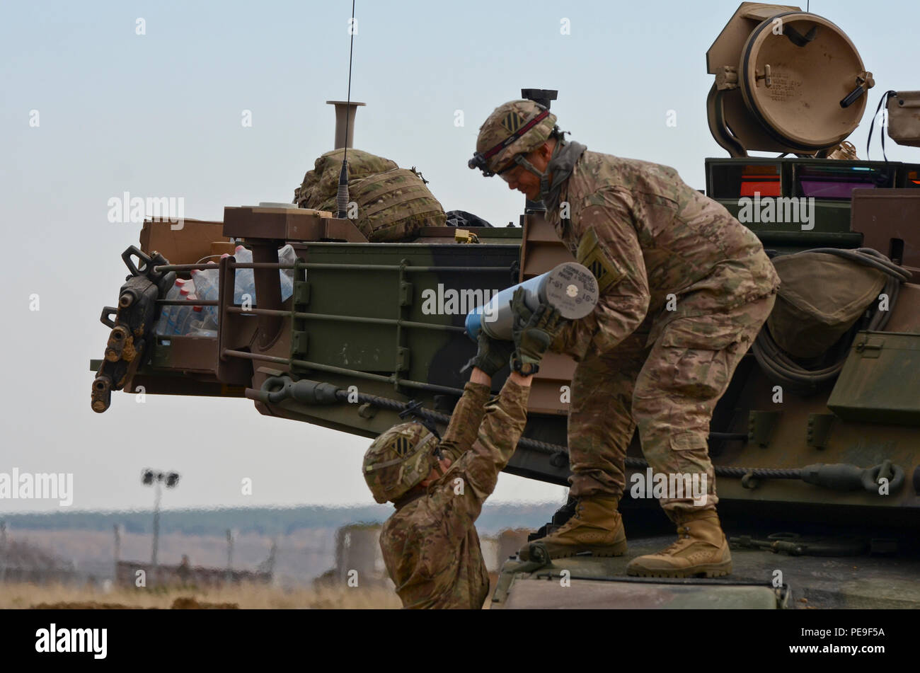 Pfc. Austin HinoJosa, a Delta Company motor transport operator, originally from Leawood, Kan., hands a 120mm round to 2nd Lt. Hemaloto Tatafu, a Delta platoon leader, from Kahuku, Hawaii, both of 1st Armored Brigade Combat Team, attached to 5th Squadron, 7th Cavalry Regiment, 3rd Infantry Division, stationed at Fort Stewart, Ga., during a field training exercise in support of Operation Atlantic Resolve at Novo Selo Training Center, Bulgaria, Nov. 17, 2015. (U.S. Army photo by Staff Sgt. Steven M. Colvin/Released) - Stock Image