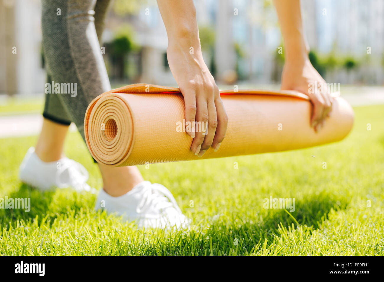 Yoga mat being put on the grass - Stock Image