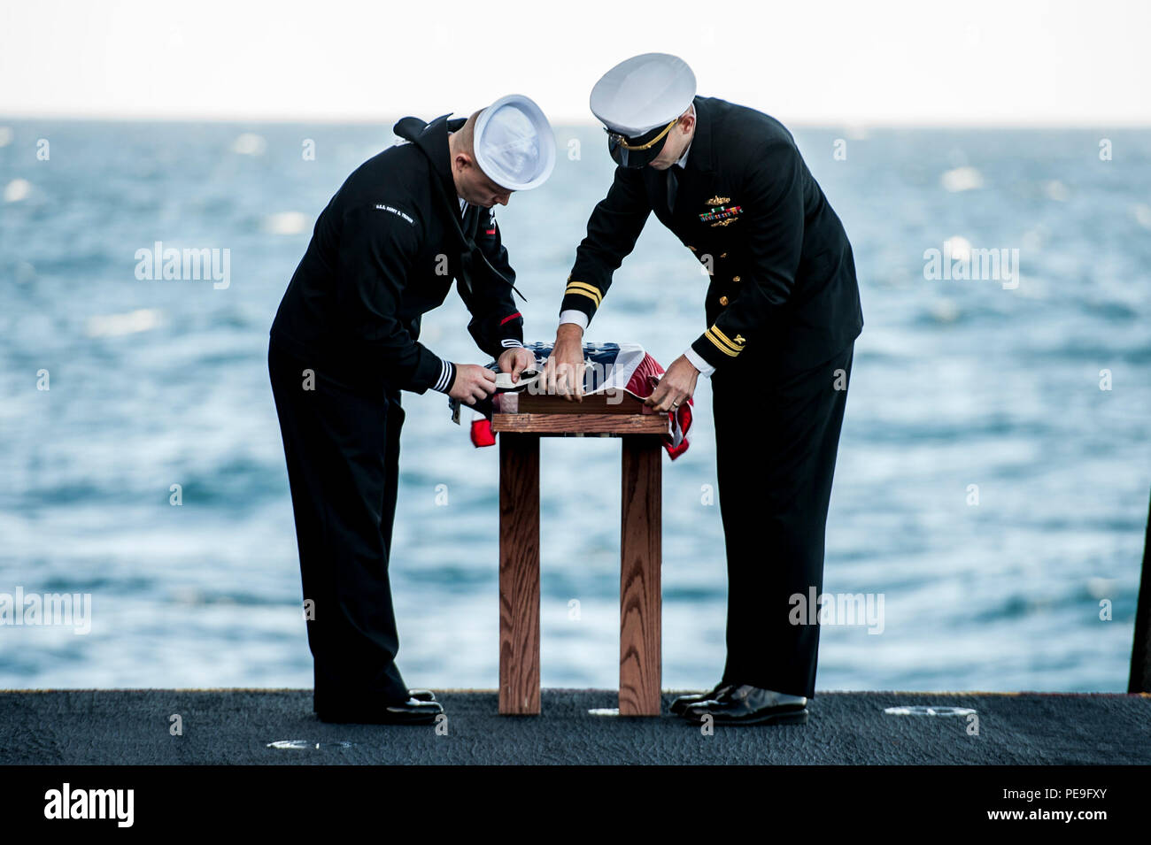 151118-N-GK939-092 ATLANTIC OCEAN (Nov. 18, 2015) Hospital Corpsman 3rd Class C. Lamacchia, left, and Lt. A. Urech participate in a burial at sea ceremony aboard aircraft carrier USS Harry S. Truman (CVN 75). Harry S. Truman Strike Group is deployed to support maritime security operations and theater security cooperation efforts in the U.S. 5th and 6th Fleet areas of operation. (U.S. Navy photo by Mass Communication Specialist Seaman L. A. Preston/Released) - Stock Image
