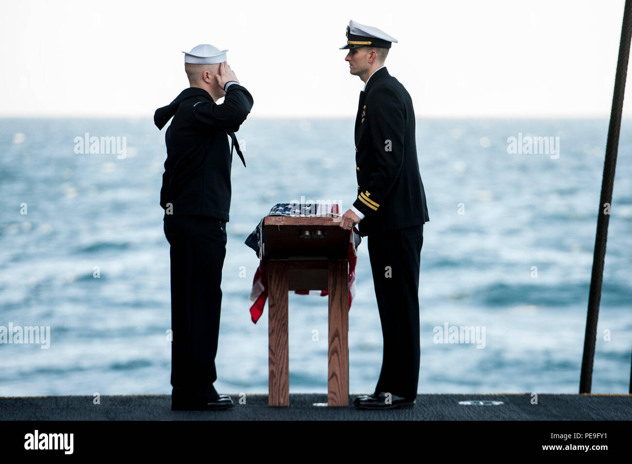 151118-N-GK939-096 ATLANTIC OCEAN (Nov. 18, 2015) Hospital Corpsman 3rd Class C. Lamacchia, left, and Lt. A. Urech participate in a burial at sea ceremony aboard aircraft carrier USS Harry S. Truman (CVN 75). Harry S. Truman Strike Group is deployed to support maritime security operations and theater security cooperation efforts in the U.S. 5th and 6th Fleet areas of operation. (U.S. Navy photo by Mass Communication Specialist Seaman L. A. Preston/Released) - Stock Image
