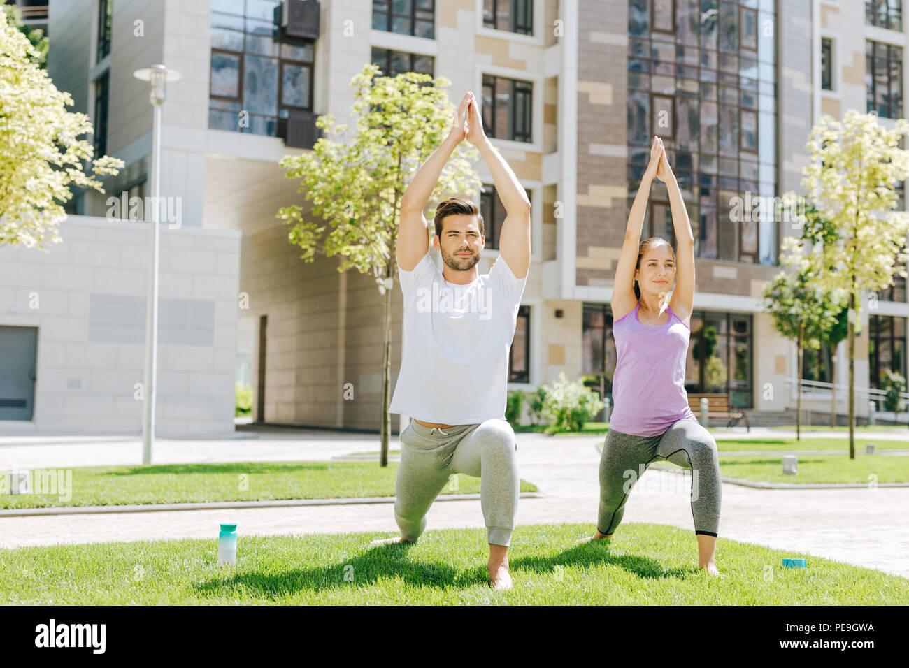 Joyful sporty people doing sport exercises - Stock Image