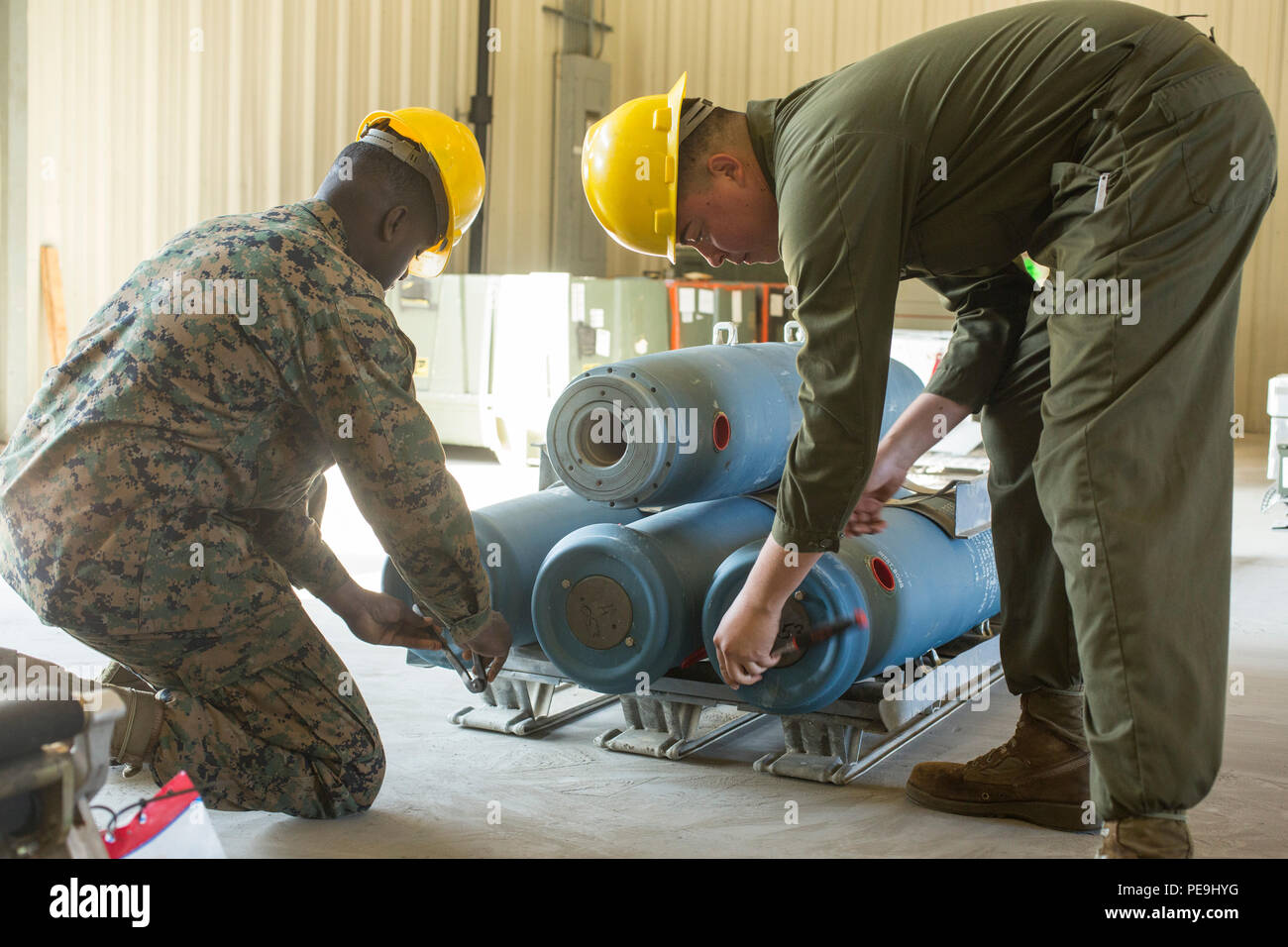U.S. Marine Corps Lance Cpl. William H. Shaw, left, and Lance Cpl. Michaelalan Mills, aviation ordnance systems technicians assigned to Marine Aviation Logistics Squadron (MALS) 14, assemble bomb dummy units on Marine Corps Air Station Cherry Point, N.C., Nov. 18, 2015. MALS-14 provides support to aviation units in 2nd Marine Aircraft Wing by preparing munitions and repairing weapon systems. (U.S. Marine Corps photo by Lance Cpl. Jered T. Stone/Released) - Stock Image